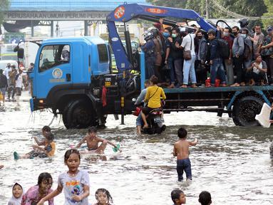 Pekerja kawasan Pelabuhan Nizam Zachman, Muara Baru menumpang kendaraan besar untuk melintasi genangan banjir rob, Jakarta, Jumat (5/6/2020). Banjir rob di Pelabuhan Muara Baru tersebut terjadi akibat cuaca ekstrem serta pasang air laut. (Liputan6.com/Helmi Fithriansyah)