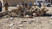 Personel keamanan dan penduduk berkumpul di sekitar lokasi bom mobil yang menargetkan markas besar polisi Afghanistan di Feroz Koh, ibu kota Ghor. (AFP)