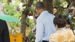 Barack Obama menunggu kelapa yang sedang di buka di sepanjang Sungai Mekong di Luang Prabang, Laos (7/9). Obama menjadi presiden AS pertama yang mengunjungi Laos dan mendarat di Vientiane akhir pada 5 September. (AFP PHOTO/SAUL Loeb)