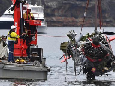 Kepolisian New South Wales dan petugas penyelamat mengangkat bangkai pesawat amfibi yang jatuh di Sungai Hawkesbury, utara Sydney, Kamis (4/1). Bangkai kapal diangkat dari dasar sungai ke sebuah tongkang. (Mick Tsikas/AAP Images via AP)