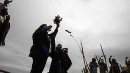 Masyarakat Adat Mapuche mengambil bagian dalam ritual selama gerhana matahari total di Carahue, La Araucania, Chile, Senin (14/12/2020). Gerhana matahari total terlihat dari Chile dan wilayah Patagonia utara Argentina. (AP Photo/Esteban Felix)