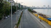 Jalan sepi di Marine Drive terlihat selama pembatasan yang diberlakukan oleh pemerintah negara bagian di tengah meningkatnya kasus corona Covid-19, di Mumbai, Kamis (15/4/2021). Kasus virus corona baru di India mencapai rekor tertinggi pada Rabu, 14 April. (Punit PARANJPE / AFP)