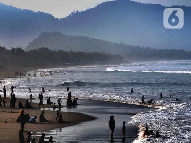 Wisatawan beraktifitas di pinggir pantai di kawasan Pantai Karang Naya, Pelabuhan Ratu, Sukabumi, Selasa (1/6/2021). Walaupun liburan lebaran telah usai sejumlah pantai di kawasan Pelabuhan Ratu masih dipadati pengunjung yang berasal dari Kota Jakarta dan Jawa Barat.(merdeka.com/Arie Basuki)