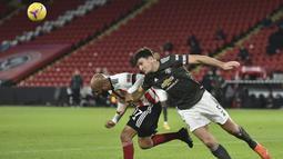 Bek Manchester United,  Harry Maguire berebut bola dengan pemain Sheffield United, David McGoldrick pada pertandingan Liga Inggris di stadion Bramall Lane, Inggris, Jumat (18/12/2020). MU tertinggal cepat di menit ke-5 lewat gol dari David McGoldrick. (AP Photo/Peter Powell)