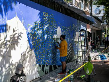 Seniman mural komunitas Converse All Stars melukis dinding Institut Perancis Indonesia (IFI) di Jalan MH. Thamrin, Jakarta, Rabu (2/12/2020). Dalam aksinya, seniman mural melukis dengan cat khusus ramah lingkungan yang diklaim bisa mengurangi polutan udara berbahaya. (Liputan6.com/Faizal Fanani)