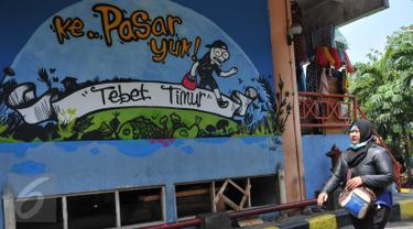 Pengunjung melintas di dekat lukisan mural di Pasar PSPT, Tebet, Jakarta (14/11/2015). Keberadaan seni mural di pasar ini bisa membuat pengunjung tersenyum. (Liputan6.com/ Gempur M Surya)