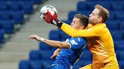 Kiper RB Leipzig, Peter Gulacsi, berebut bola dengan gelandang Hoffenheim, Christoph Baumgartner, pada laga lanjutan Bundesliga peka ke-30 di Rhein-Neckar Arena, Sabtu (13/6/2020) dini hari WIB. Leipzig menang 2-0 atas Hoffenheim. (AFP/Uwe Anspach/Pool)