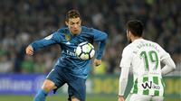 Gaya bintang Real Madrid, Cristiano Ronaldo (kiri) melewati adangan pemain Real Betis, Antonio Barragan pada lanjutan La Liga Santander di Villamarin stadium,Seville, (18/2/2018). Real Madrid menang 5-3. (AFP/Cristina Quicler)