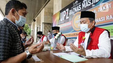 Amil zakat mendoakan umat muslim yang membayar zakat fitrah di Masjid Istiqlal, Jakarta, Jumat (7/5/2021). Panitia Zakat Masjid Istiqlal mulai membuka layanan pembayaran zakat fitrah dengan pembayaran senilai Rp 50 ribu atau 3,5 liter beras. (Liputan6.com/Faizal Fanani)
