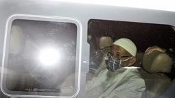 Abu Bakar Baasyir duduk di dalam sebuah van setelah dibebaskan dari Lapas Gunung Sindur, Kabupaten Bogor, Jawa Barat, Jumat (8/1/2021). Abu Bakar Baasyir nampak mengenakan pakaian serba putih, kaca mata, dan masker dalam minibus putih Hyundai berpelat nomor AD 1138 WA. (AP Photo/Aditya Irawan)