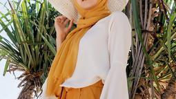 Saat liburan, Ellen tampil dengan hijab panjang berwarna oranye dipadukan dengan celana panjang berwarna seragam dan baju berwarna putih. (Liputan6.com/IG/@ellennitaa)