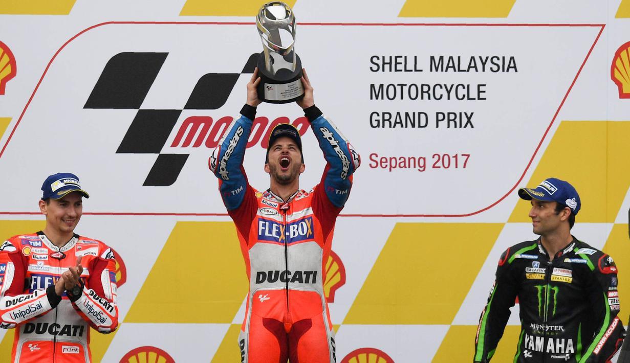 Pebalap Ducati, Andrea Dovizioso, melakukan selebrasi usai menjuarai balapan MotoGP Malaysia di Sirkuit Sepang, Minggu (29/10/2017). Dovizioso finis pertama dengan catatan waktu 44 menit 51,497 detik. (AFP/Mohd Rasfan)