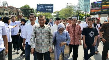 Mantan Wakil Presiden Jusuf Kalla atau JK (kiri) didampingi istrinya Mufidah berjalan kaki saat tiba di kampung halamannya, Makassar, Sulawesi Selatan, Sabtu (26/10/2019). JK disambut meriah warga Makassar. (Liputan6.com/HO/Tim JK)