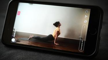 Seorang guru yoga mengajar kelas live yang disiarkan di akun Instagram-nya pada hari kesembilan belas selama lockdown yang bertujuan untuk membatasi penyebaran infeksi COVID-19 yang disebabkan oleh coronavirus novel di Paris, Prancis (4/4/2020). (AFP/Philippe Lopez)