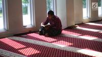 Seorang umat muslim membaca Alquran di Masjid Al-Madinah, Parung, Bogor, Selasa (7/5/2019). Sejumlah umat muslim meningkatkan ibadah pada bulan suci Ramadhan 1440 H dengan membaca Alquran (tadarus), shalat berjamaah, berdoa dan dzikir di masjid. (merdeka.com/Arie Basuki)