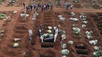 Petugas dengan pakaian pelindung menurunkan peti mati seseorang yang meninggal karena komplikasi COVID-19 ke dalam kuburan di pemakaman Vila Formosa di Sao Paulo, Brasil, Rabu (7/4/2021). Sao Paulo pada Rabu mulai menggali 600 kuburan tambahan setiap hari di pemakaman kotanya (AP Photo/Andre Penner)