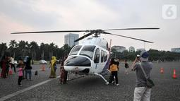 Warga berfoto dengan helikopter Polri yang terparkir di kawasan Monas, Jakarta, Rabu (16/10/2019). Kehadiran empat helikopter TNI/Polri yang akan digunakan dalam apel pengamanan pelantikan presiden dan wakil presiden tersebut menarik perhatian pengunjung Monas. (merdeka.com/Iqbal Nugroho)