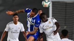 Penyerang Alaves, Joselu berebut bola dengan bek Real Madrid, Ferland Mendy pada lanjutan Liga Spanyol di stadion Alfredo di Stefano, Sabtu (11/7/2020). Real Madrid menang 2-0 lewat gol Karim Benzema dan Marco Asensio. (GABRIEL BOUYS/AFP)