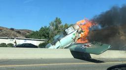 Kendaraan melintas di dekat pesawat antik Amerika Utara AT-6 yang terbakar di US 101 di Agoura Hills, California (23/10). Kecelakaan menyebabkan kemacetan panjang sekitar 50 km di sebelah barat pusat kota Los Angeles. (AFP Photo/Cynthia Alvarez)