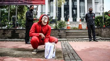 Seorang mahasiswa dari Mahasiswa Independen secara simbolis membakar salinan naskah UU Cipta Kerja di depan Gedung MK, Jakarta, Selasa (27/10/2020). Mahasiswa menyatakan aksi tersebut bentuk ketidakpercayaan kepada MK bila proses uji materi UU Cipta Kerja dilakukan. (Liputan6.com/Faizal Fanani)