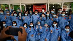 Tenaga medis mengenakan pita merah di seragamnya memberi hormat tiga jari di Rumah Sakit Umum Yangon di Yangon (3/2/2021). Petugas kesehatan di 70 rumah sakit dan departemen medis di Naypyidaw, Yangon dan kota-kota lain mengatakan, mereka tidak akan bekerja di bawah rezim militer. (STR / AFP)