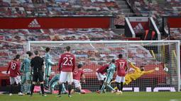 Tendangan bebas pemain Manchester United, Bruno Fernandes (kiri) berhasil menjebol gawang Liverpool pada laga babak keempat FA Cup 2020-21 di Old Trafford, Senin (25/01/2021). (Foto: AP/Pool/Laurence Griffiths)