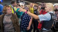 Petugas kepolisian memberi penjelasan kepada calon penumpang di aula terminal 1 Bandara Frankfurt, Jerman, Selasa (7/8). Sejumlah penerbangan harus dibatalkan setelah seorang yang tak dikenal menyusup melewati pos pemeriksaan. (Boris Roessler/dpa via AP)