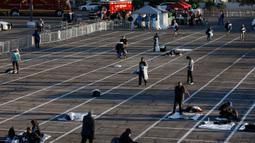 Orang-orang bersiap tidur di tempat-tempat yang ditandai dengan kotak-kotak yang diberi jarak untuk social distancing di lahan parkir di Las Vegas, Senin (30/3/2020). Tempat parkir itu diubah menjadi tempat penampungan sementara untuk para tunawisma di ttengah pandemi Covid-19. (AP/John Locher)