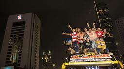 Suporter Persija Jakarta, The Jakmania, melakukan pesta juara Liga 1 dengan konvoi menuju Bundaran Hotel Indonesia, Jakarta, Minggu (9/12). Persija unggul satu poin dari PSM Makassar di puncak klasemen. (Bola.com/Vitalis Yogi Trisna)