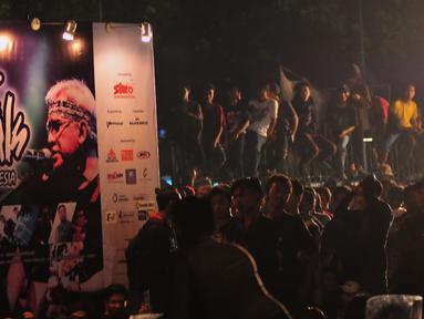 Suasana saat konser Iwan Fals berlangsung di luar Istora Senayan, Jakarta, Sabtu (21/11/2015). Keadaan penonton terlihat kondusif dan aman. Para Oi bernyanyi bersama dan mengibarkan bendera Oi saat acara berlangsung. (Liputan6.com/Faisal R Syam)