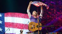 Vokalis grup band Coldplay, Chris Martin mengibarkan bendera Amerika Serikat saat menghibur para penonton di Lapangan FedEx di Landover, Md, AS (6/8). (Photo by Brent N. Clarke/Invision/AP)