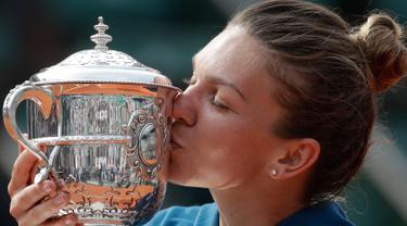 Petenis Rumania, Simona Halep mencium trofi Grand Slam seusai menang atas petenis AS, Sloane Stephens pada babak final Prancis Terbuka 2018 di stadion Roland Garros, Sabtu (9/6). Halep berhasil meraih gelar grand slam pertamanya. (AP/Alessandra Tarantino)