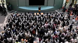 Sejumlah peserta berkumpul mengikuti simulasi evakuasi anti-rudal di taman hiburan Tokyo Dome City, Jepang, (22/1). Simulasi digelar untuk melatih warga Jepang untuk siap menghadapi rudal yang bisa mengancam setiap waktu. (AFP Photo/Toshifumi Kitamura)