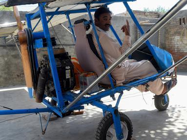 Muhammad Fayyaz duduk dalam pesawat buatannya di Desa Tabur, Provinsi Punjab, Pakistan, 8 April 2019. Penjual popcorn asal sebuah desa di Pakistan tersebut sukses membuat pesawat sendiri dari alat seadanya. (ARIF ALI/AFP)