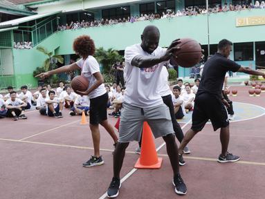 Legenda NBA, Jason Richardson, memberikan pelatihan kepada siswa SMA 82 Jakarta, Kamis (28/3). Kunjungan peraih dua gelar juara kontes slamdunk NBA tersebut merupakan bagian dari rangkaian program Jr NBA. (Bola.com/M Iqbal Ichsan)