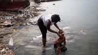 Seorang wanita memandikan putrinya di pantai saat mereka bersiap-siap untuk pergi ke gereja, di Warf of Port Cite Soleil di Port-au-Prince, Haiti (17/3). Cité Soleil merupakan lingkungan yang sangat miskin dan padat penduduk. (AP Photo/Dieu Nalio Chery)