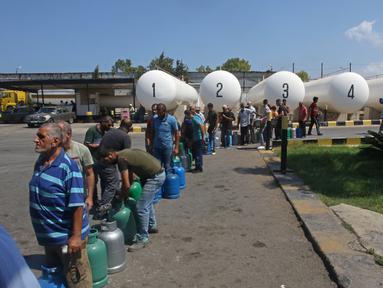 Warga Lebanon menunggu untuk mengisi tabung gas di kota selatan Sidon, Selasa (10/8/2021). Warga Lebanon harus mengantre panjang demi membeli gas untuk memasak di tengah krisis ekonomi parah yang memicu kelangkaan berbagai kebutuhan pokok dari obat-obatan hingga bahan bakar. (Mahmoud ZAYYAT/AFP)