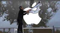 Aktivis Asosiasi Perpajakan Transaksi Keuangan dan Aksi Warga Negara (ATTAC) memasang poster di jendela toko Apple saat berunjuk rasa di luar toko Apple saat peluncuran iPhone X di Aix-en- Provence, Prancis (3/11). (AFP Photo/Anne-Christine Poujoulat)