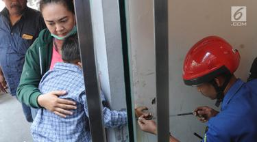 Petugas Damkar dari Pos Pesanggrahan berusaha menyelamatkan tangan murid TK, Fathur yang terjepit kaca pintu ATM Bank BNI di Jalan M. Saidi, pesanggrahan, Jakarta Selatan, Senin (5/8/2019). Fathur terjepit pintu saat ibunya mengambil uang di ATM tersebut. (merdeka.com/Arie Basuki)