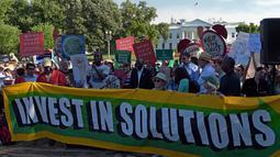 Demonstran membawa spanduk saat aksi di dekat Gedung Putih di Washington, AS, Kamis (1/6). Demonstran memprotes keputusan Donald Trump yang menarik AS dari perjanjian Paris tentang perubahan iklim yang disepakati pada 2015. (AP/ Susan Walsh)