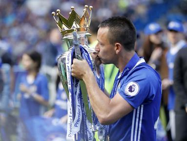 Kapten Chelsea, John Terry, mencium tropi Premier League 2016/2017 usai laga melawan Sunderland di Stamford Bridge, Minggu (21/5/2017). Terry resmi mengakhiri kiprahnya selama 22 tahun di Chelsea. (AP/Frank Augstein)