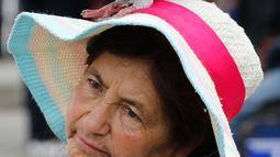 Burung merpati bertengger di kepala penjual jagung di Bolivar Square, Bogota, 2 Oktober 2018. Pemerintah Bogota berusaha mengurangi populasi merpati melalui larangan bagi pengunjung untuk tidak memberi makan lagi burung-burung itu. (AP/Fernando Vergara)