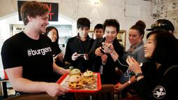"""Pengunjung memfoto burger berkarakter pokemon di restoran Down N 'Out Burger, Sydney, Australia, (26/8).  Restoran ini menyebut burger kreasi mereka dengan sebutan """"Pokeburg"""". (REUTERS/Jason Reed)"""