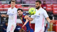 Penyerang Barccelona, Lionel Messi, berebut bola dengan bek Real Madrid, Nacho Fernandez, pada laga lanjutan Liga Spanyol di Camp Nou Stadion, Sabtu (24/10/2020) malam WIB. Real Madrid menang 3-1 atas Barcelona. (AFP/Lluis Gene)