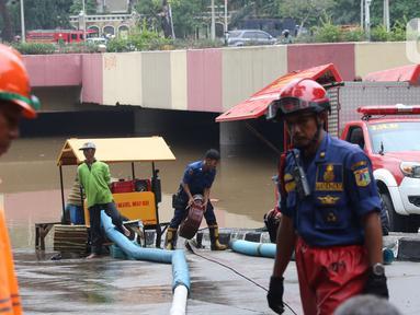 Petugas melakukan penyedotan air yang merendam underpass Kemayoran, Jakarta, Minggu (2/2/2020). Akibat hujan yang cukup lama di kawasan tersebut membuat underpass tersebut terendam air hingga ketinggian 5 meter. (Liputan6.com/Angga Yuniar)