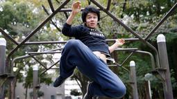 Ekspresi Juni Sato saat melompat unjuk kemampuan parkournya di sebuah taman di Tokyo, Jepang (2/11). Parkour sendiri adalah seni bergerak dan berpindah dari satu tempat ke tempat lainnya, dengan efisien dan secepat-cepatnya. (Reuters/Kim Kyung-Hoon)