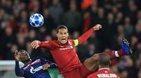 Bek Liverpool, Virgil Van Dijk berebut bola dengan pemain Red Star Belgrade, El Fardou Ben Nabouhane selama pertandingan grup C Liga Champions di stadion Anfield, Inggris (24/10). Liverpool menang telak 4-0 atas Red Star. (AP Photo/Jon Super)