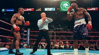 Mike Tyson dan Evander Holyfield kembali berduel di MGM Grand Garden Arena, Las Vegas pada 28 Juni 1997. Akan tetapi, laga akbar ini harus dihentikan pada ronde ketiga, karena Tyson menggigit kuping Holyfield. (AFP/JEFF HAYNES)