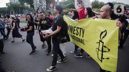 Aktivis yang tergabung dalam Amnesty Internasional Indonesia menggelar aksi di depan Istana Negara, Jakarta, Selasa (10/12/2019). Dalam aksi tersebut aktivis memberikan bingkisan kepada Sekretariat Kabinet yang berisi aspirasi masyarakat Indonesia untuk pemerintah. (Liputan6.com/Faizal Fanani)