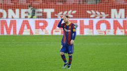 Striker Barcelona, Lionel Messi, memegang kepalanya usai ditaklukkan Sevilla pada laga leg pertama semifinal Copa del Rey di Estadio Ramon Sanchez Pizjuan, Kamis (11/2/2021). Barcelona tumbang dengan skor 2-0. (AFP/Cristina Quicler)